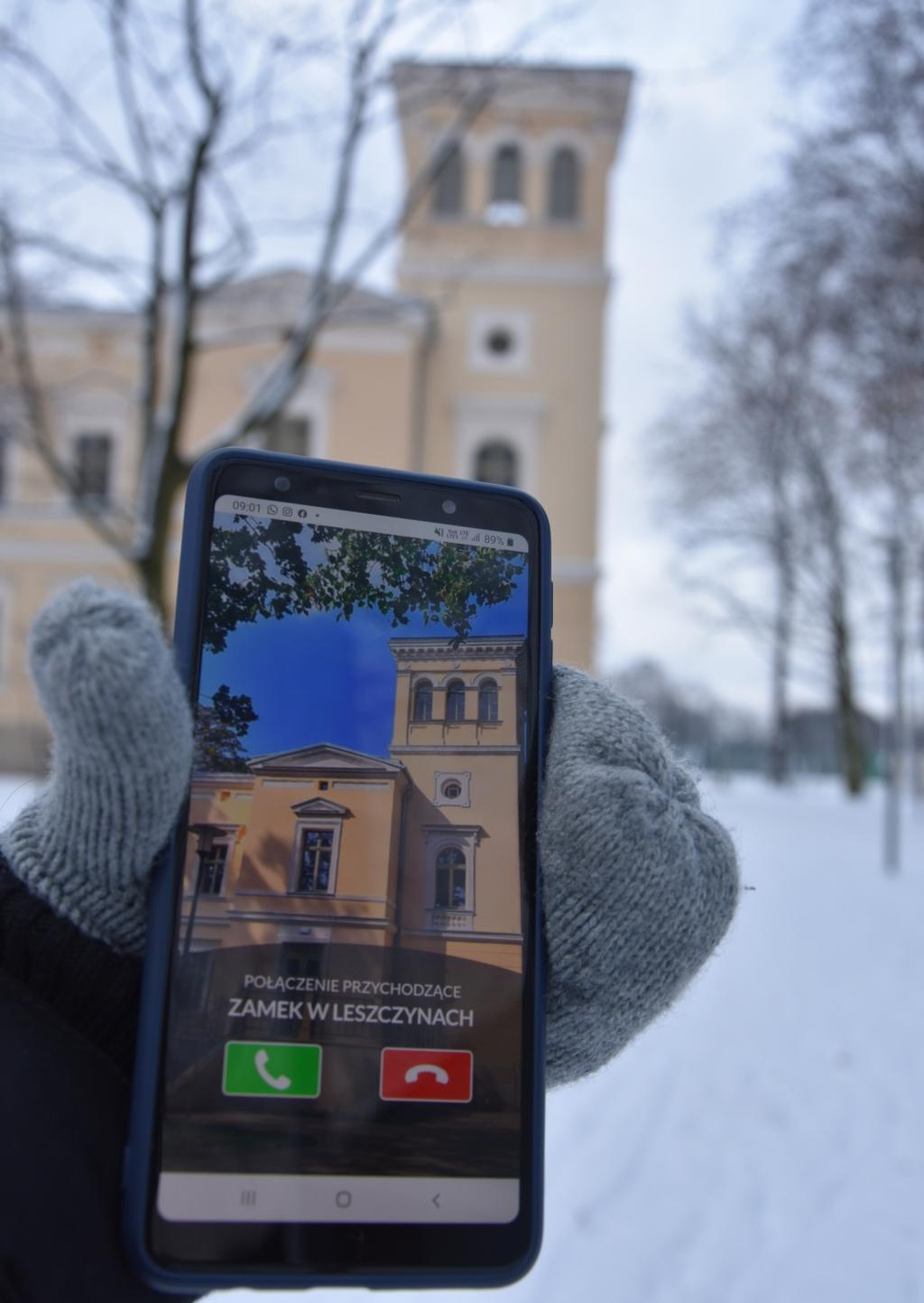 Na zdjęciu: Telefon z włączoną aplikacją Poznaj historię na tle Zameczku w Leszczynach